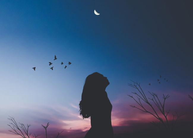 Uma mulher olhando para o céu e pensando sobre a sua vida.