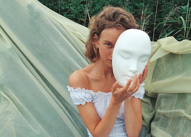 Uma mulher com uma máscara em seu rosto. Pois, ela finge gostar de algumas coisas para agradar os outros e quer mudar.