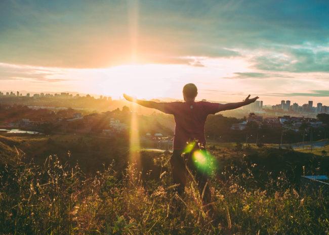 Um homem com os braços abertos para o sol, sentindo-se leve.