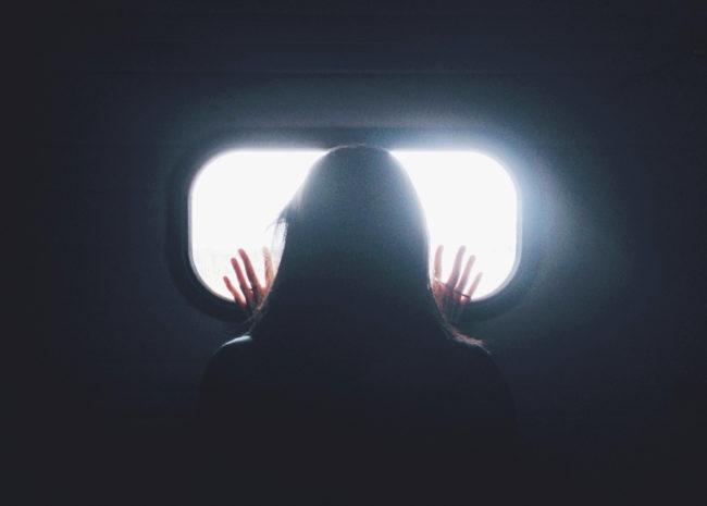 Uma mulher com as mãos em uma janela, ela está se sentindo presa e por isso quer melhorar