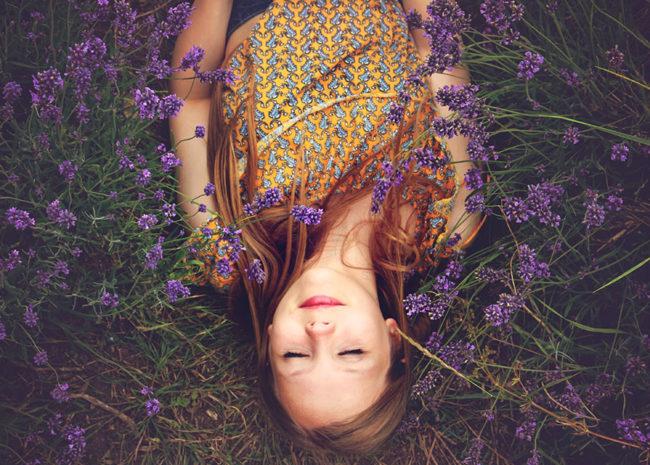 Uma menina deitada triste pois não sabe mais o que é feliz.