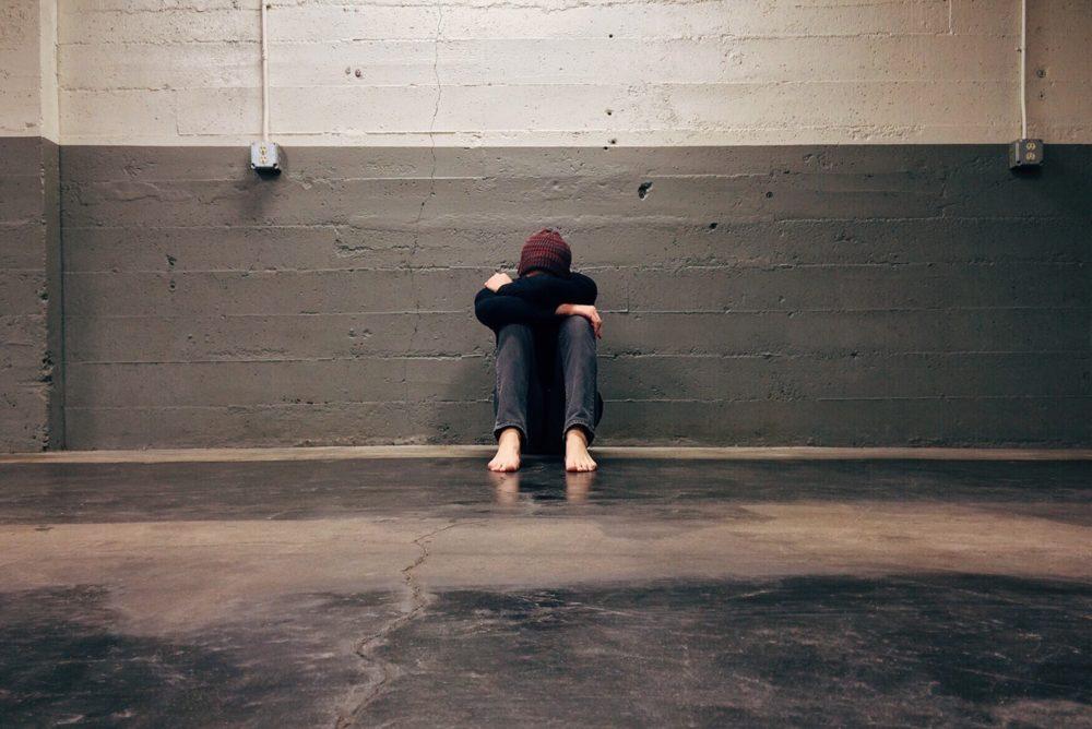 Um homem ajoelhado pois está triste e depressivo.