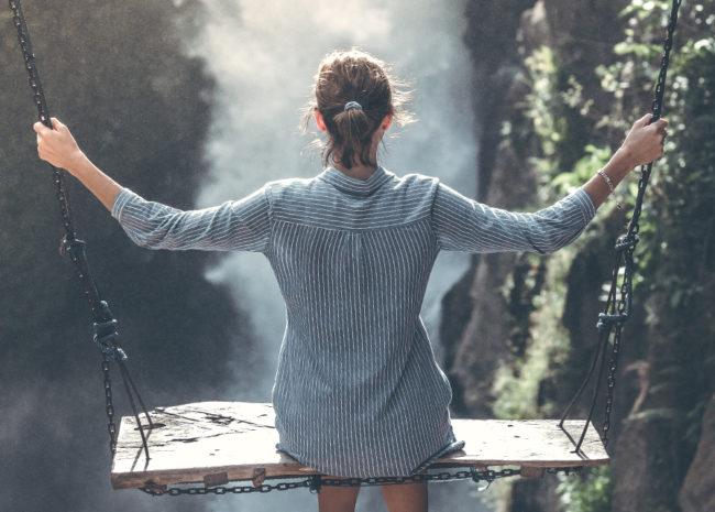 Uma mulher em um balanço se arriscando e fazendo algo novo.