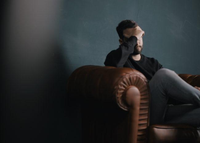 Um homem triste e com a mão no rosto pois não sabe o que fazer.