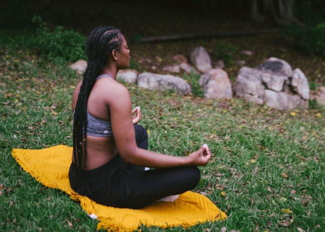 Uma mulher meditando, se sentindo muito bem.