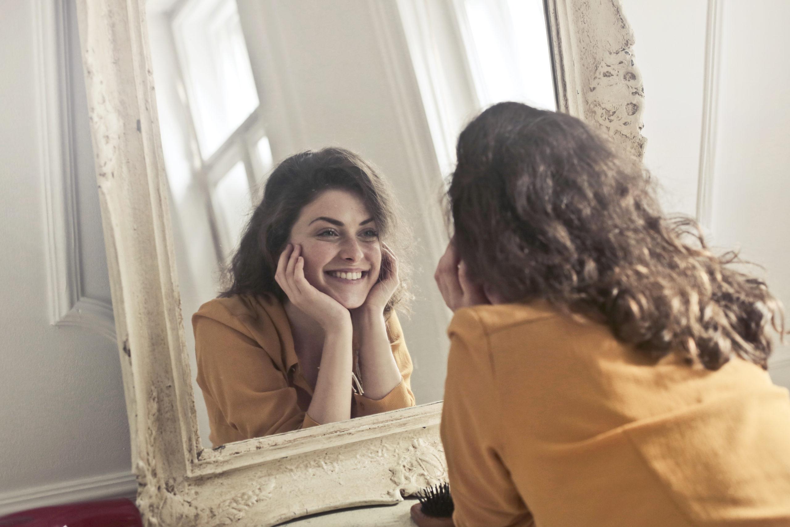 Uma mulher se olhando no espelho e sentindo o autoamor.