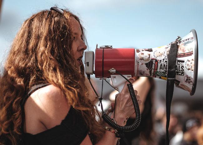 Uma mulher gritando em um megafone.
