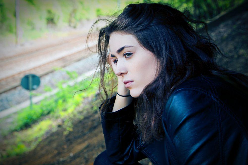 Uma mulher refletindo sobre a sua vida.