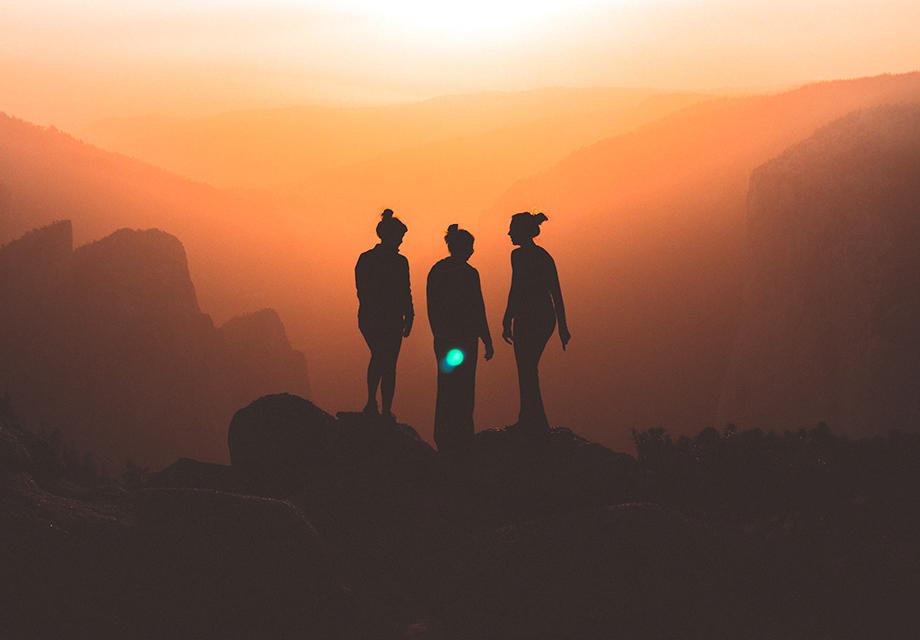 Três amigos em uma montanha conversando.