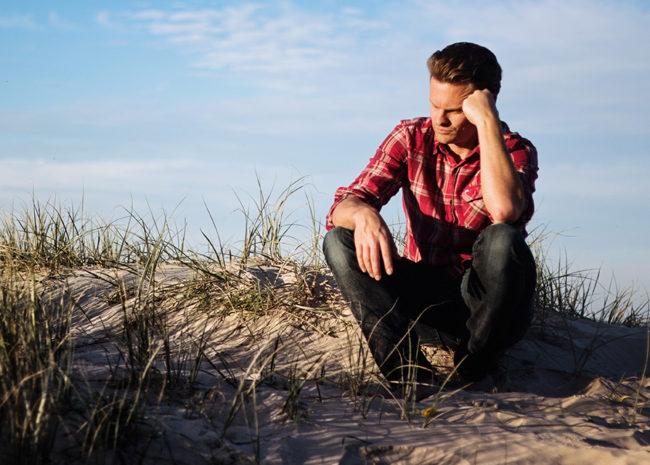 Um homem pensativo pois ele está se sentindo mal de não conseguir perdoar.