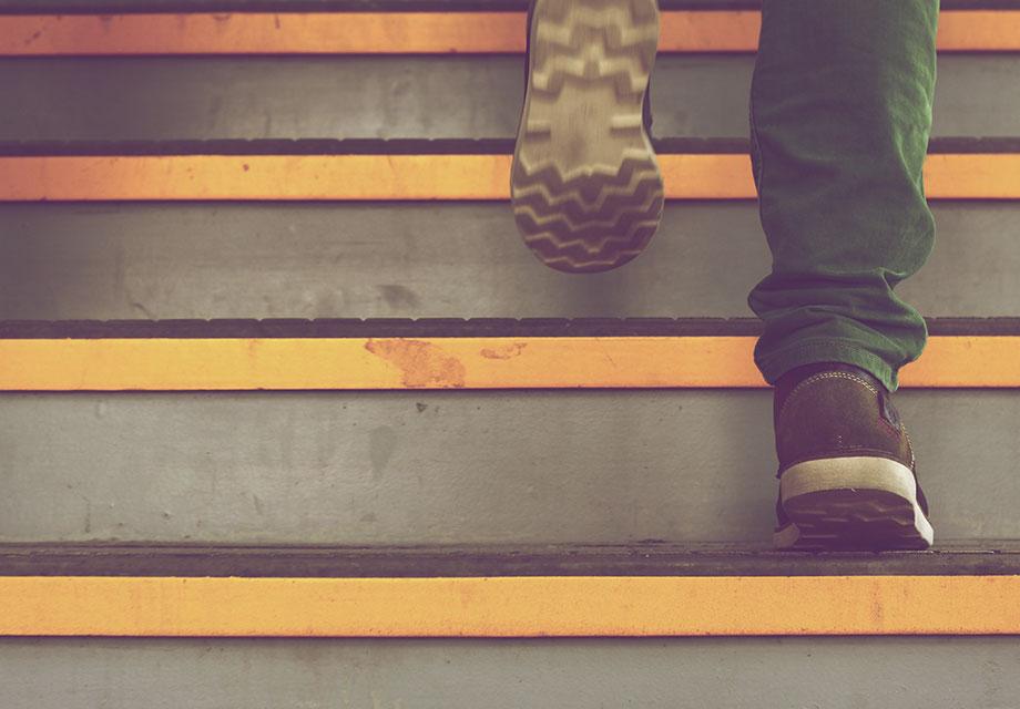Imagem dos pés de um homem subindo uma escada.