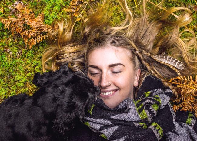 Uma mulher deitada na grama com um cachorro sorrindo.