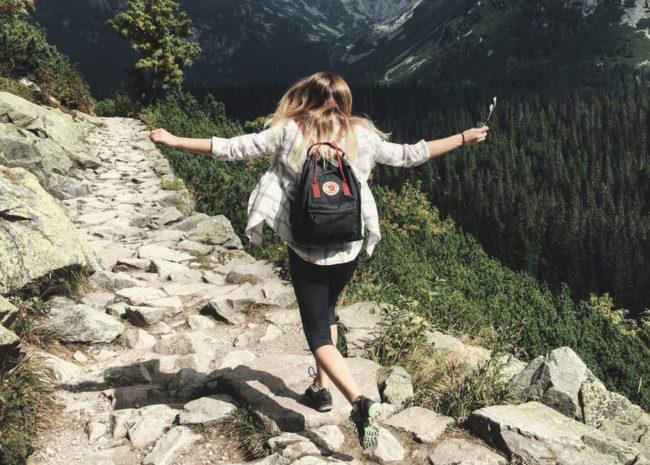 Uma mulher fazendo trilha, ela está pulando em pedra e sentido-se muito bem.