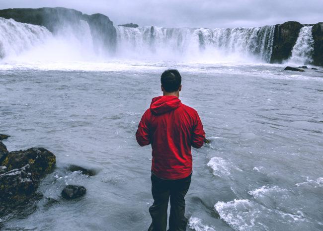 Um homem de costas olhando para uma cachoeira e refletindo sobre a sua vida.