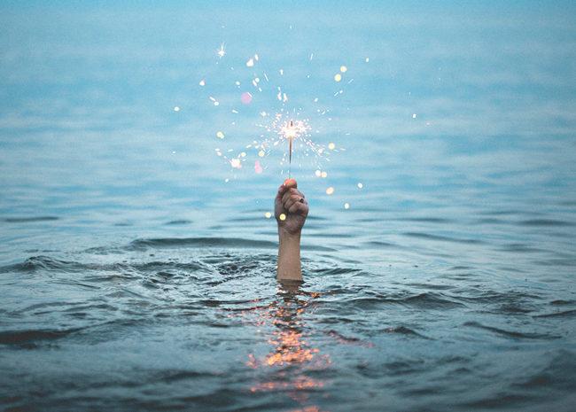 Um mar e uma mão expressando esperança.