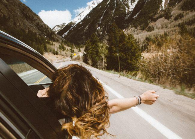 Uma mulher com a cabeça e o braço para fora do carro, ela está se sentindo livre de incertezas em sua vida.
