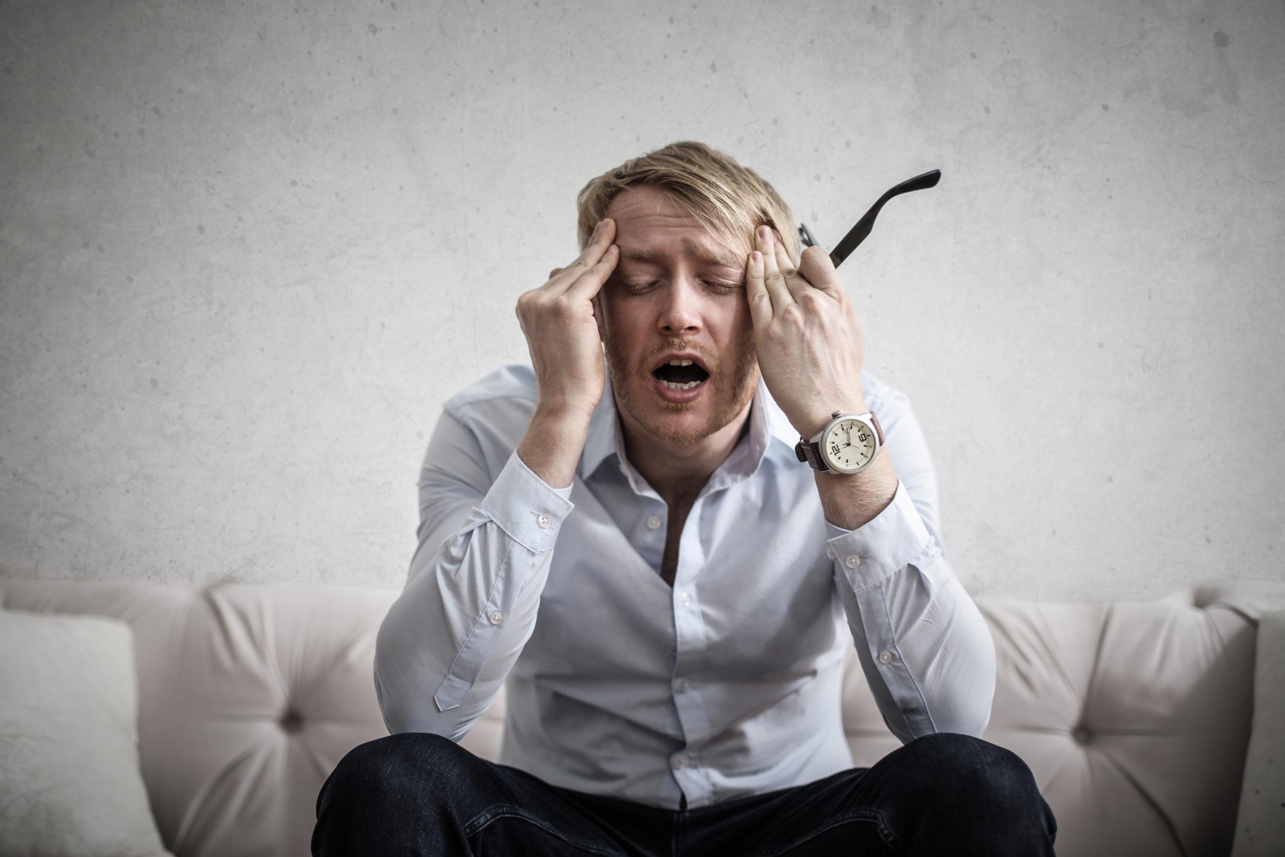 Um homem com uma expressão de estar cansado e irritado, ele está assim pois está ansioso.
