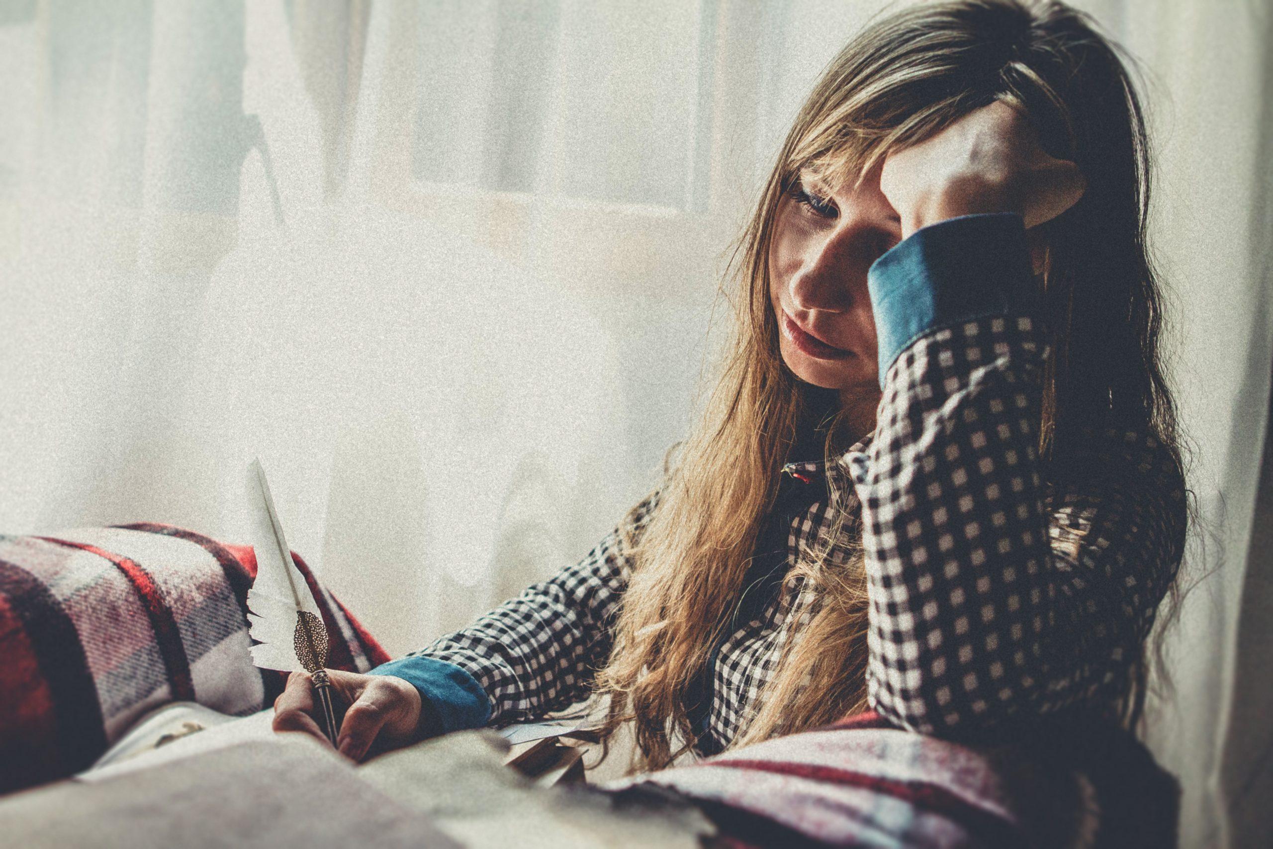 Uma mulher triste e agoniada pois está com ansiedade.