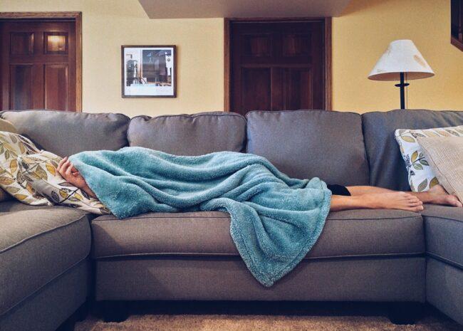 Uma pessoa deitada com sono pois não consegue dormir bem a noite, pois tem depressão.