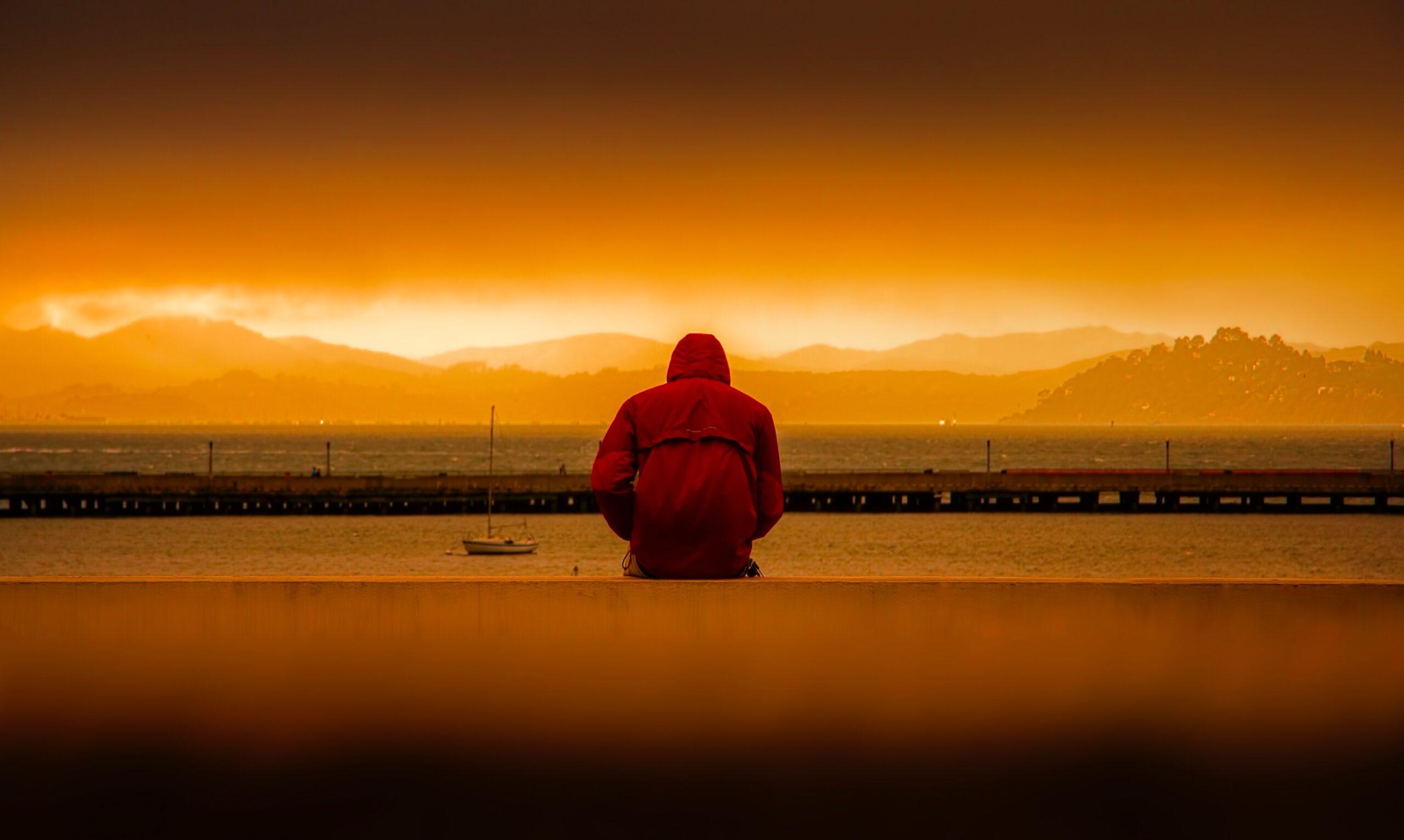 Um homem sentado longe, pois está com depressão. Ele está confuso, pois não sabe quais são os níveis da depressão.
