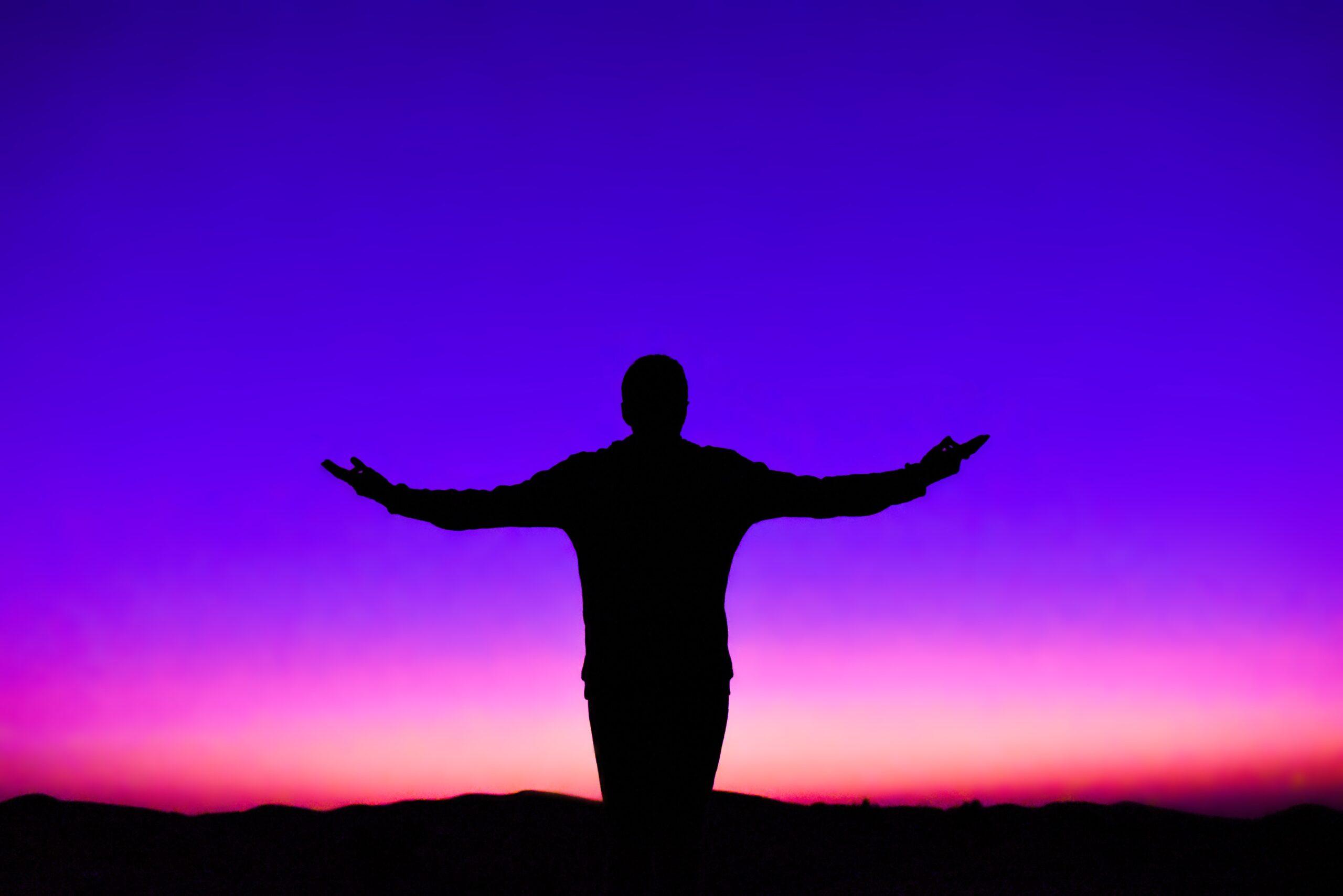 Um homem livre com os braços abertos após saber como viver melhor a vida.
